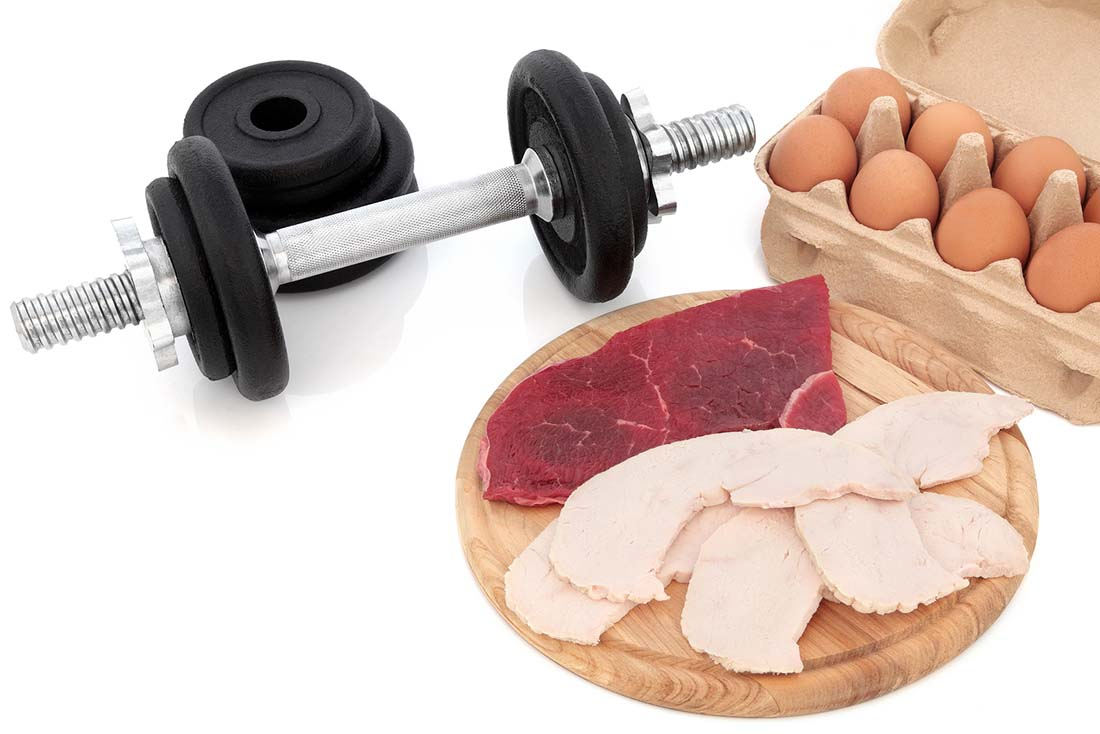 A Dumbbell Next To Eggs and Various Meat Options.