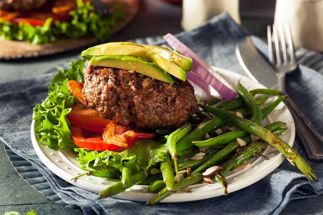 A Bunless Avocado Burger With Fresh Salad.