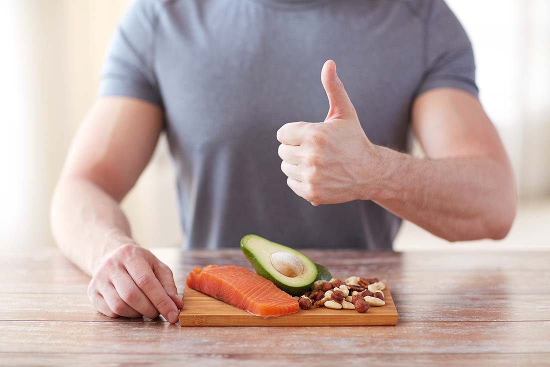 A Man With Salmon, Avocado and Nuts Doing a 'Thumbs Up' Motion.