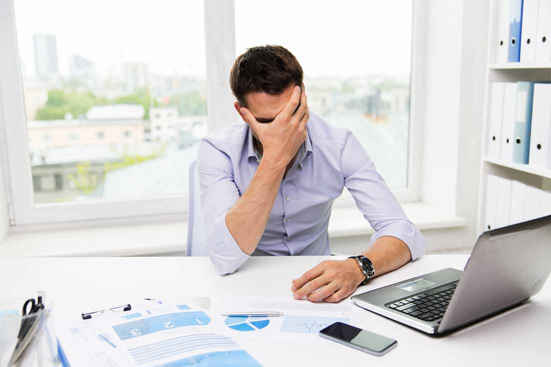 A Stressed Office Worker Holding His Head.