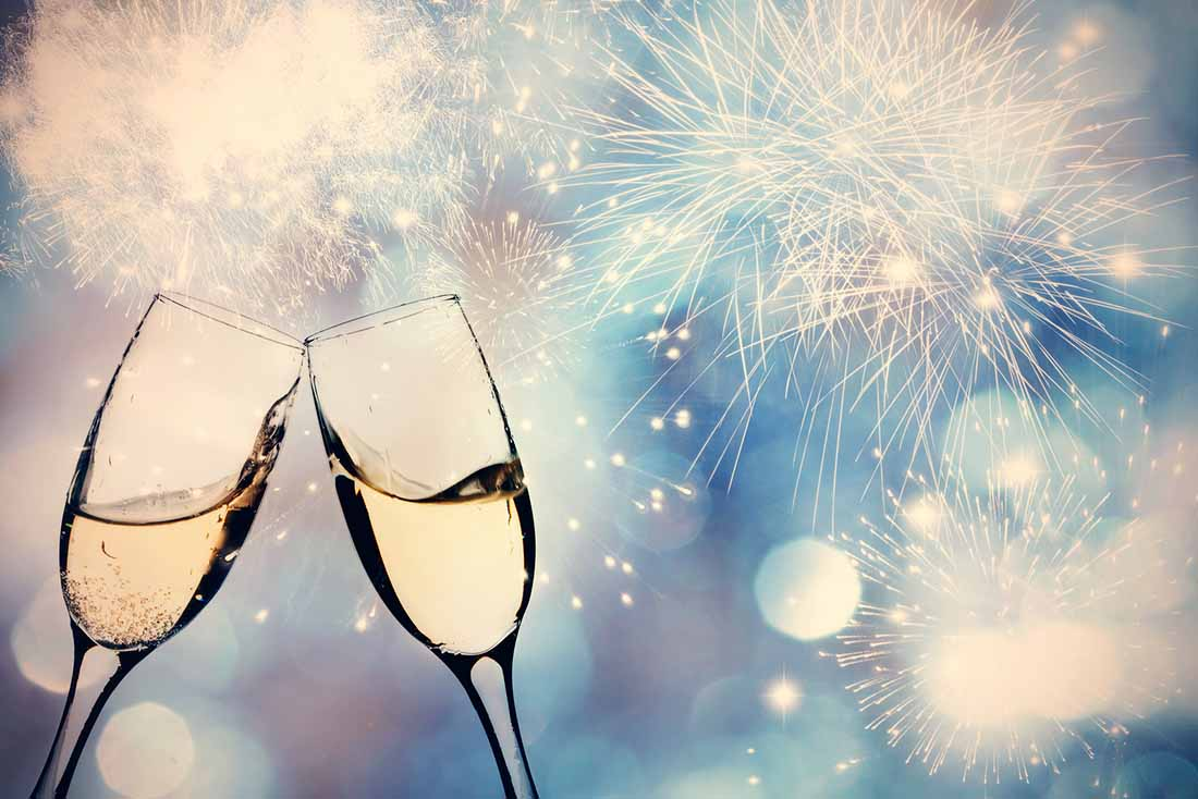 Two Champagne Glasses Touching With Fireworks in the Sky.