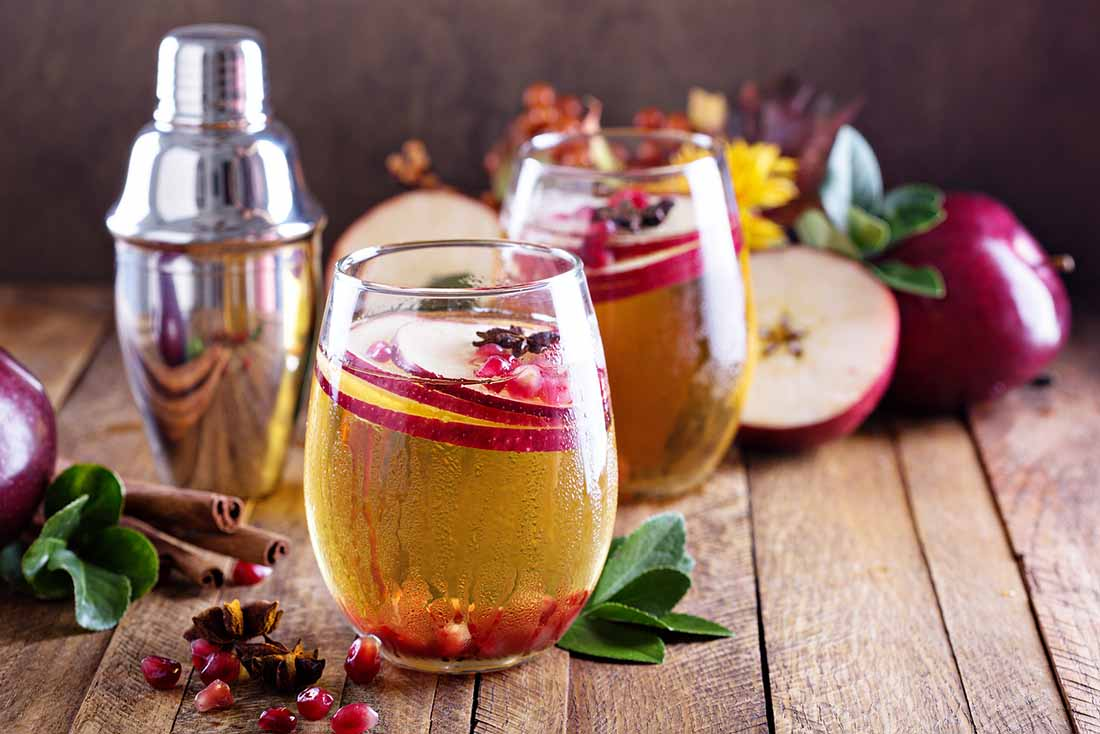 Two Glasses of Cider Next To Apples on a Wooden Surface.