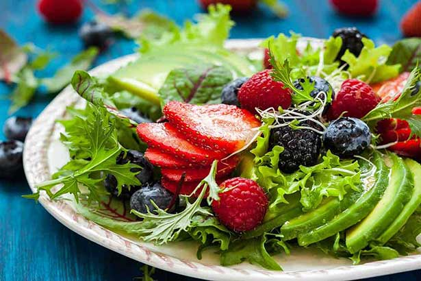 A Fruit Salad - Berries, Avocado and Salad Greens.
