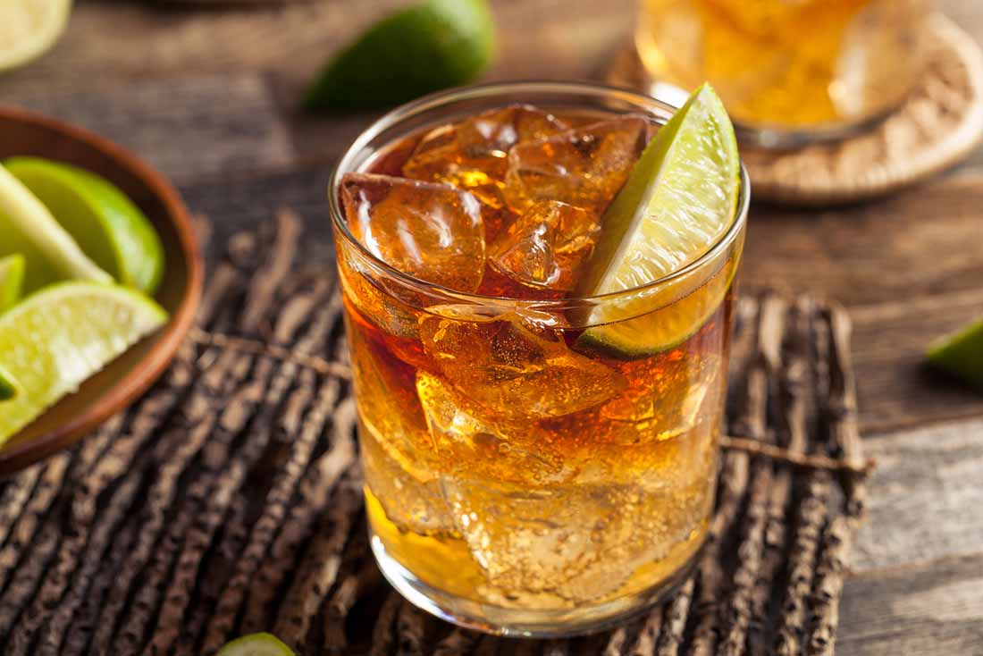 A Glass of Rum With Ice Cubes and a Slice of Lime.