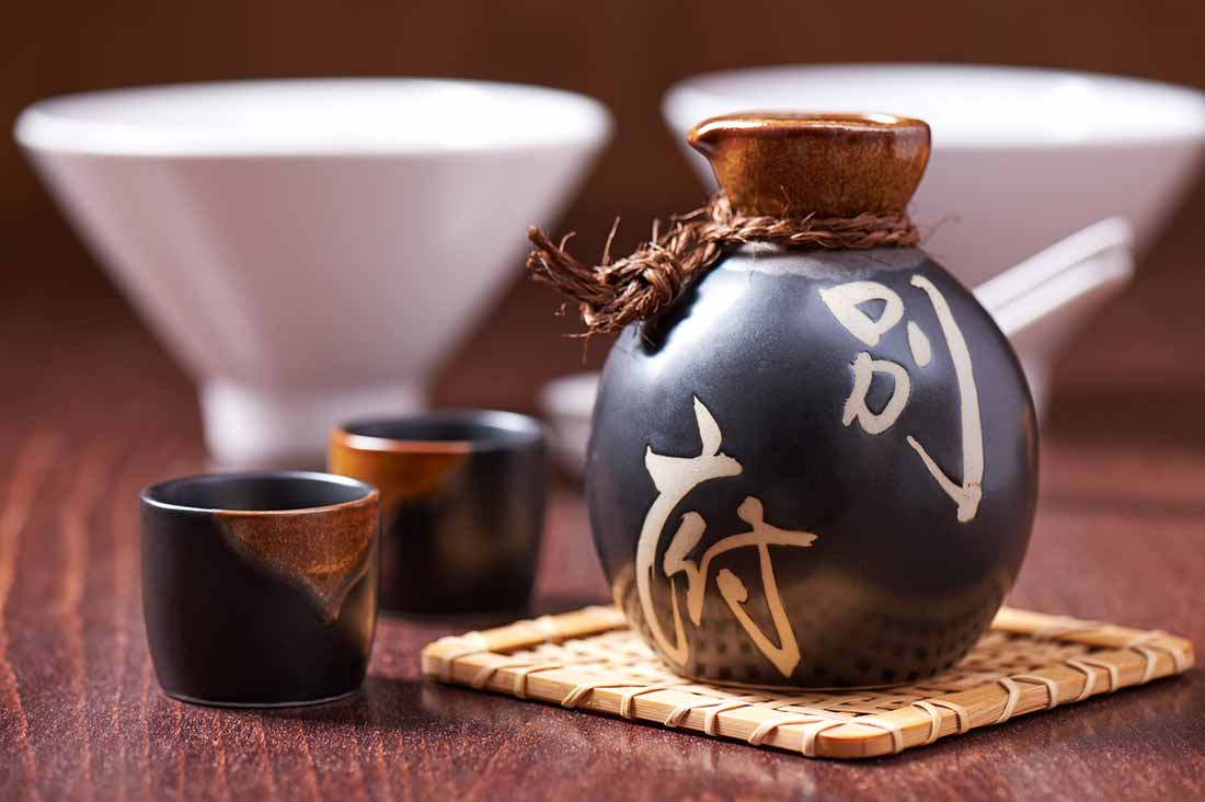 A Bottle of Japanese Sake and Two Traditional Drinking Cups.