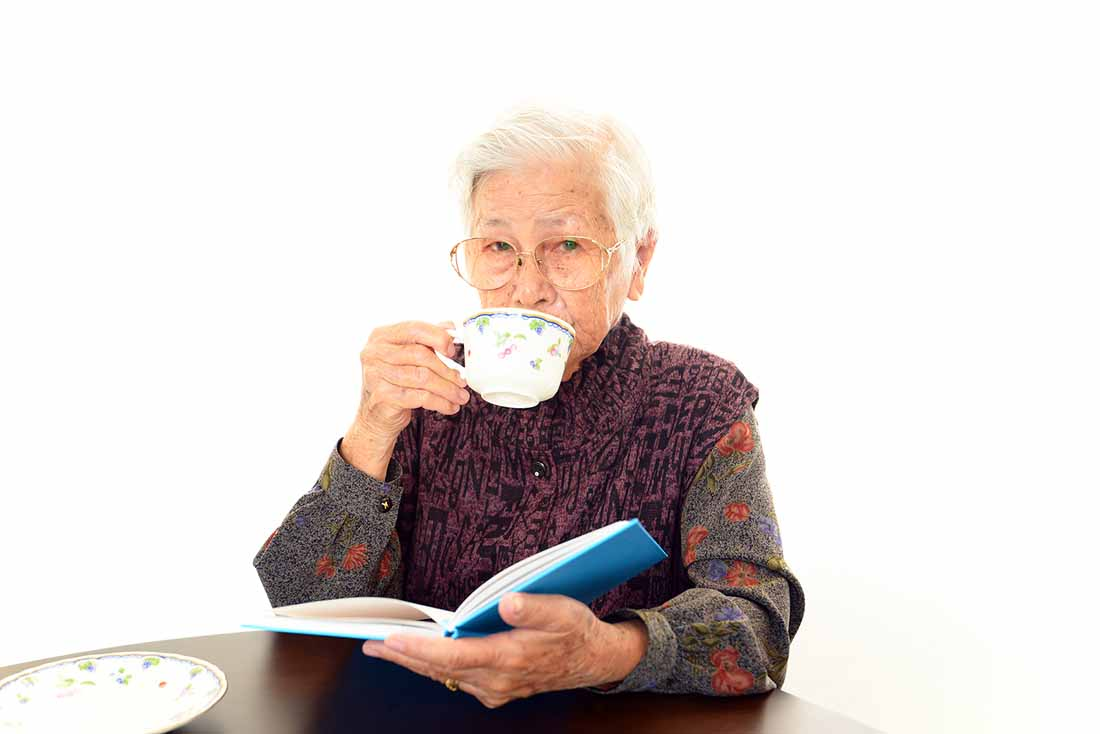 An Elderly Lady Drinking a Cup of Coffee.