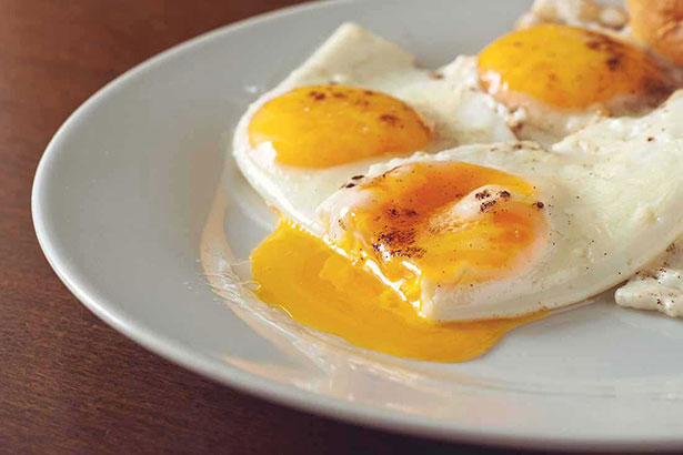 Three Fried Eggs On a Plate With Runny Egg Yolk.