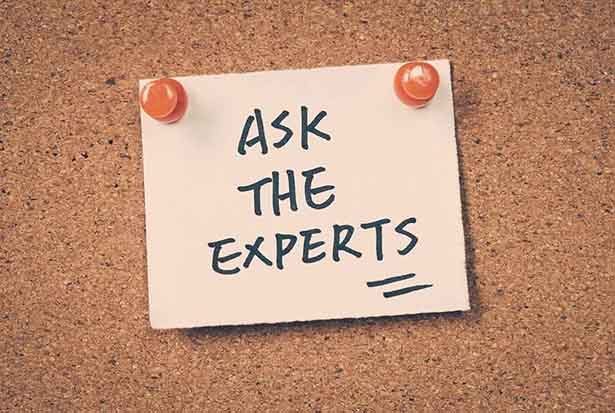 A Post-It Note On a Board Saying 'Ask the Experts'.