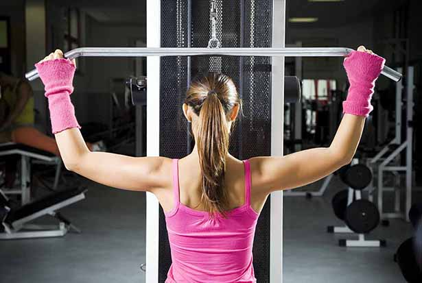 Picture of an Athletic Woman Doing Lateral Pulldown Exercise On a Gym Machine.