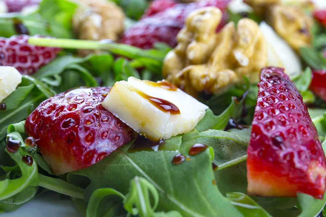 Salad Featuring Leafy Greens, Strawberries, Coconut Vinegar and Cheese.