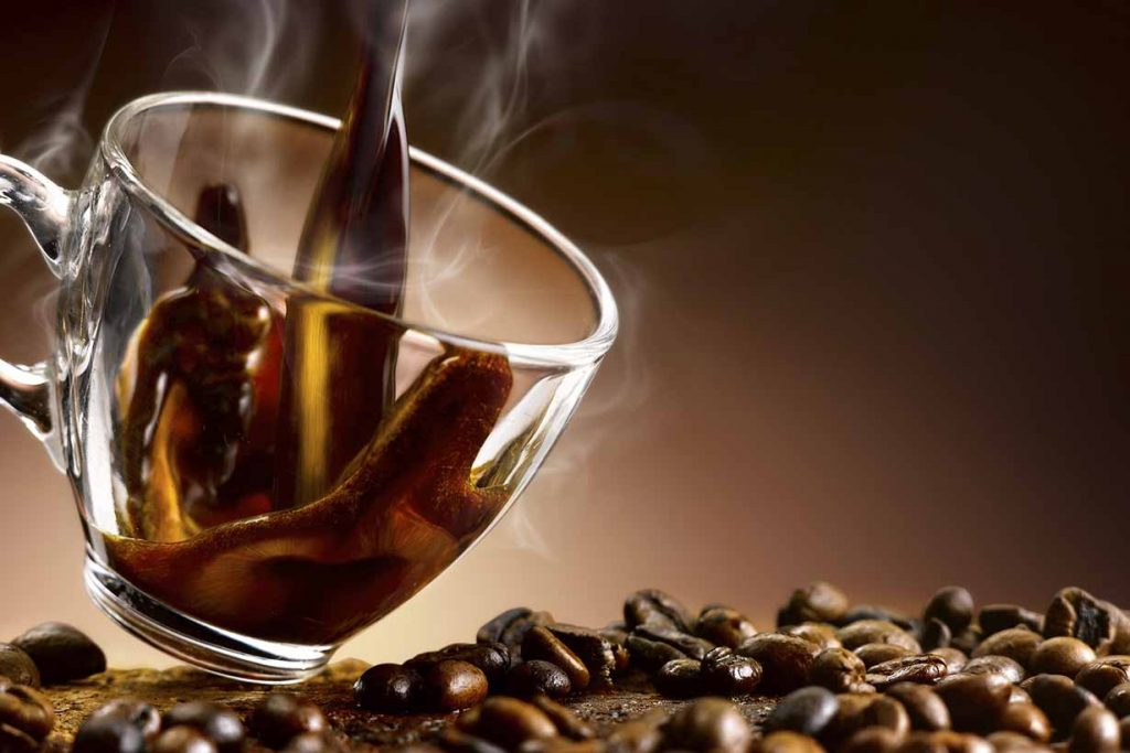 Boiling Hot Coffee Being Poured Into a Glass Cup Over Coffee Beans.