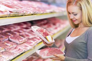 A Woman Shopping in the Grocery Store and Looking at Meat.