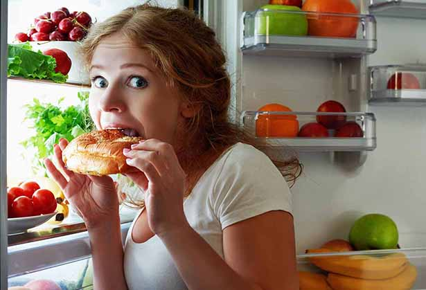 Picture of a girl secretly eating junk food from the fridge.