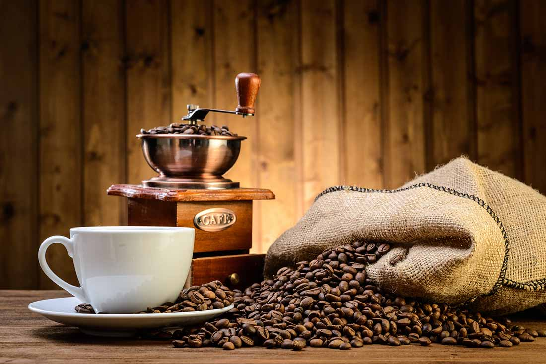A Coffee Cup, Coffee Grinder and a Sack of Coffee Beans Overspilling.