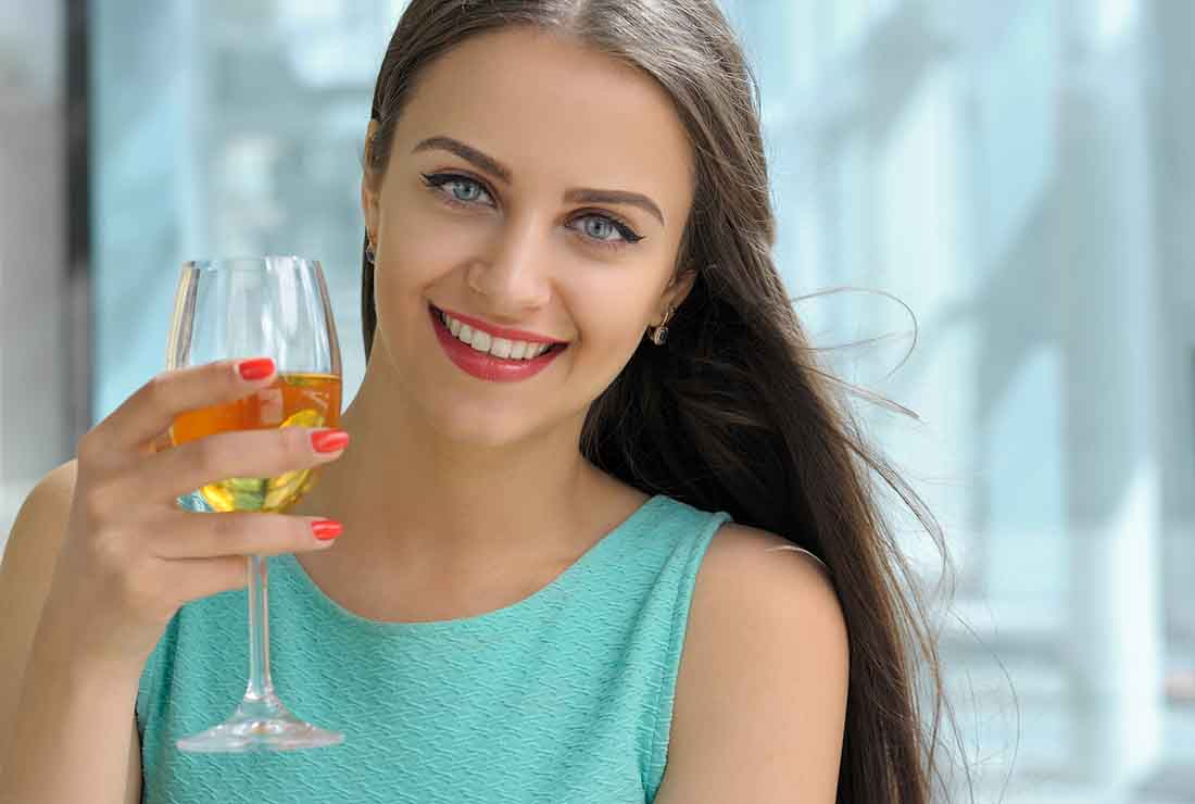 A Young Lady Drinking a Glass of White Wine.