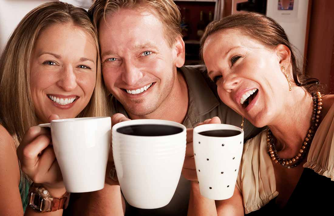Three People Smiling While Holding a Cup of Coffee Up.