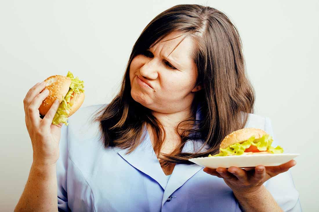 A Woman Considering Eating a Hamburger.