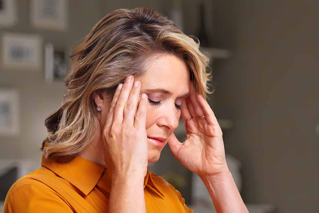 A Woman Holding Her Head Feeling Stressed.