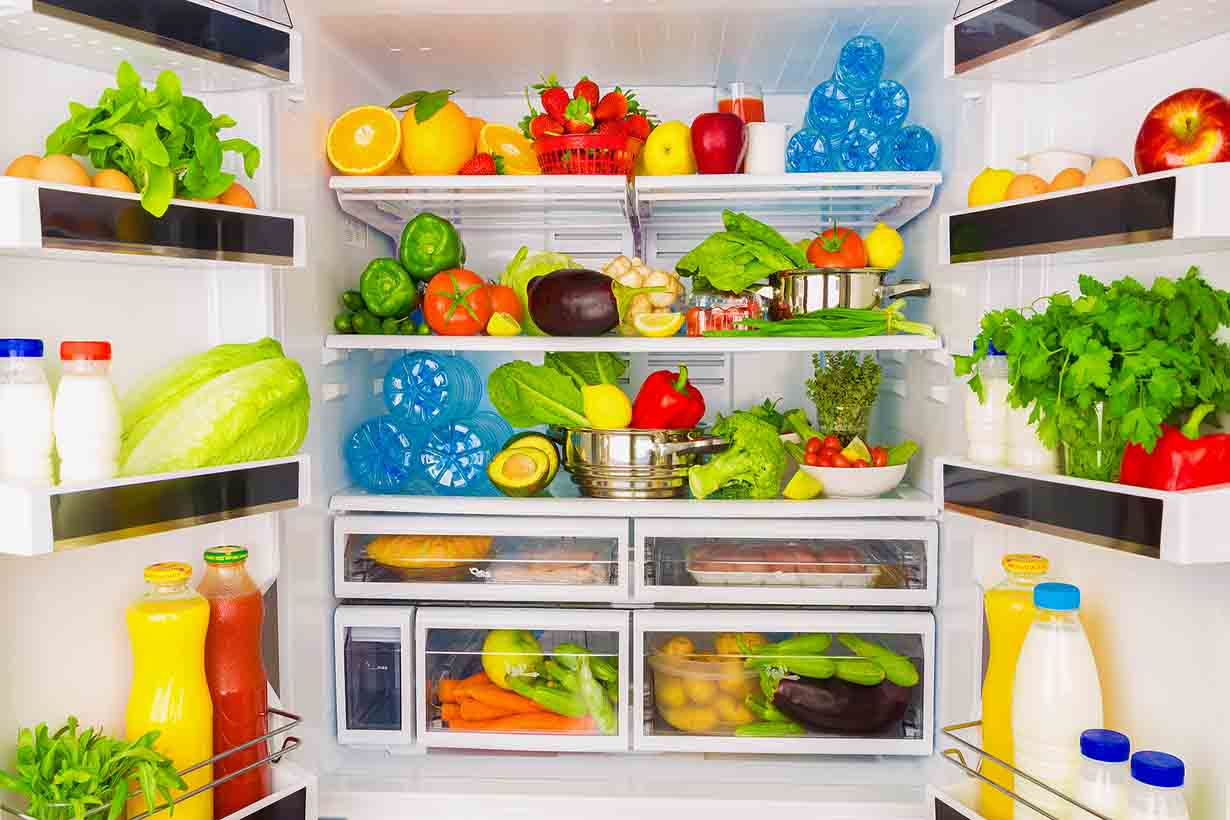 Picture of an open fridge full of lots of fresh fruit and vegetables