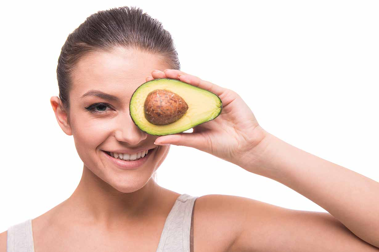 Happy woman holding an avocado
