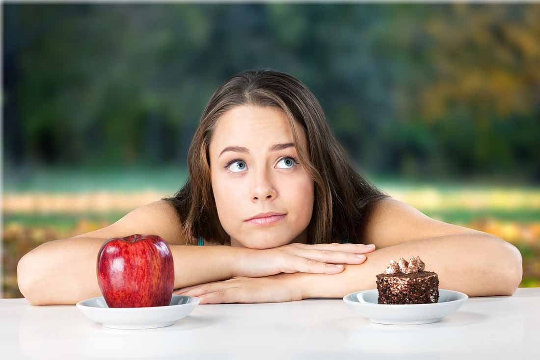 A Young Woman Choosing Between Chocolate Cake and an Apple.