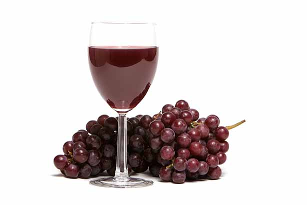 A Glass of Red Wine Next To a Bunch of Grapes.