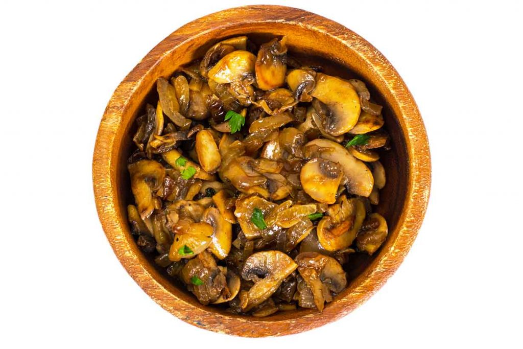 A picture of sauteed mushrooms in a wooden bowl.
