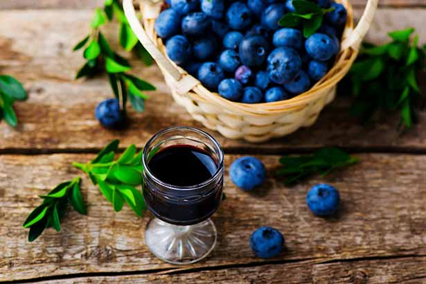 A Glass of Blueberry Wine Next To a Basket of Blueberries.