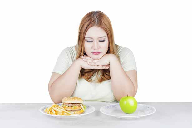 Picture of a woman choosing healthy or unhealthy food. Stress theme.