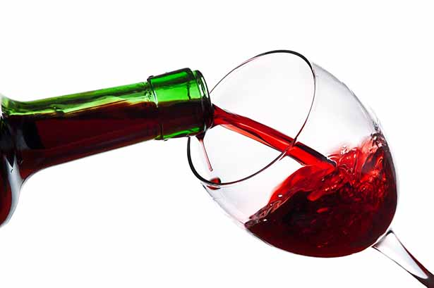 Picture of some red wine being poured into a wine glass