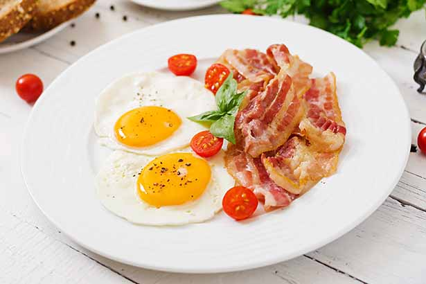 A Plate of Bacon and Eggs With Cherry Tomatoes.