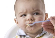 Picture of a baby being fed with commercial baby food