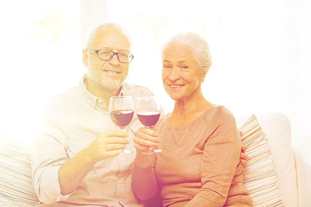 An Elderly Couple Drinking a Glass of Red Wine.