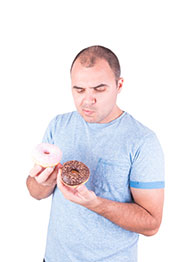 A Man Eating Two Donuts - Chocolate and Strawberry.