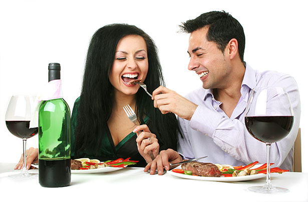Picture of a young couple enjoying a steak dinner - theme of steak is delicious