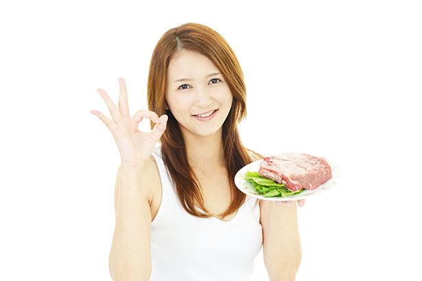 Picture of a Girl Holding Some Meat in the Air.
