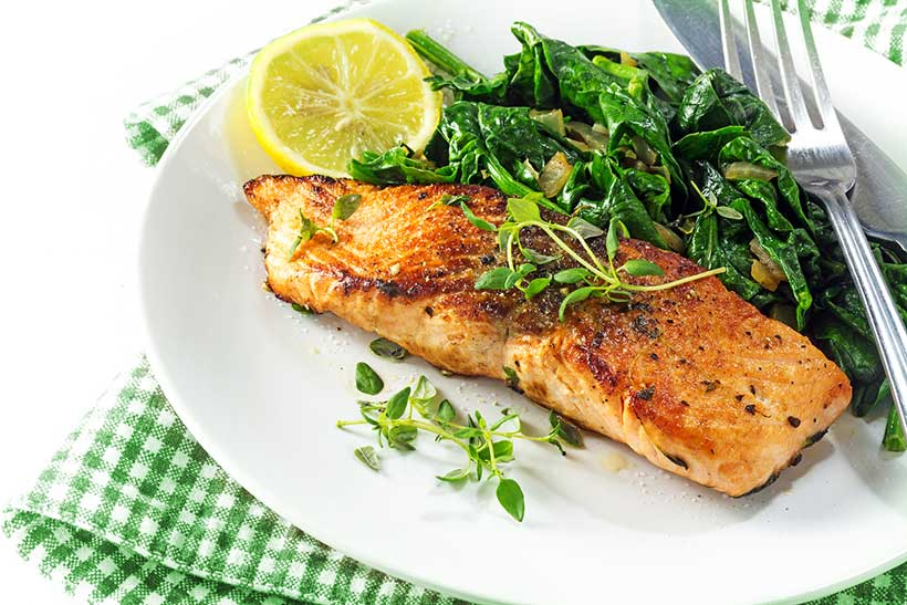 Picture of a broiled salmon fillet with a side of spinach and lemon.