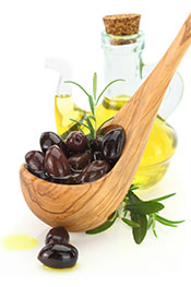 Picture of Kalamata Olives With an Olive Oil Bottle in the Background.