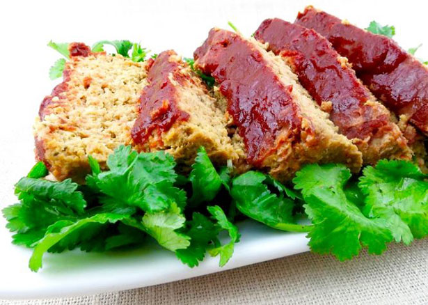 Picture of a paleo meatloaf on a bed of lettuce.