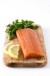 A Fillet of Salmon On a Chopping Board Alongside Lemon.