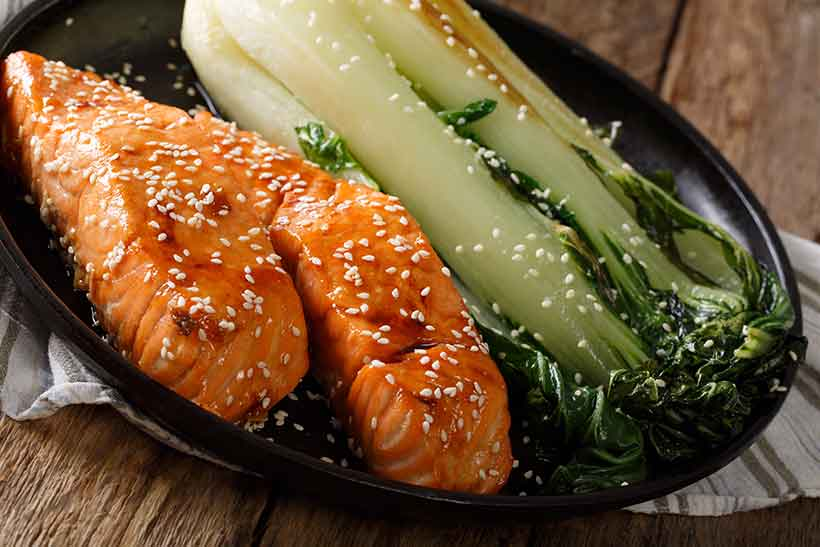 Picture of a Chinese-style steamed salmon fillet with bok choy.