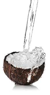 People of a fresh coconut cut in half with water splashing.