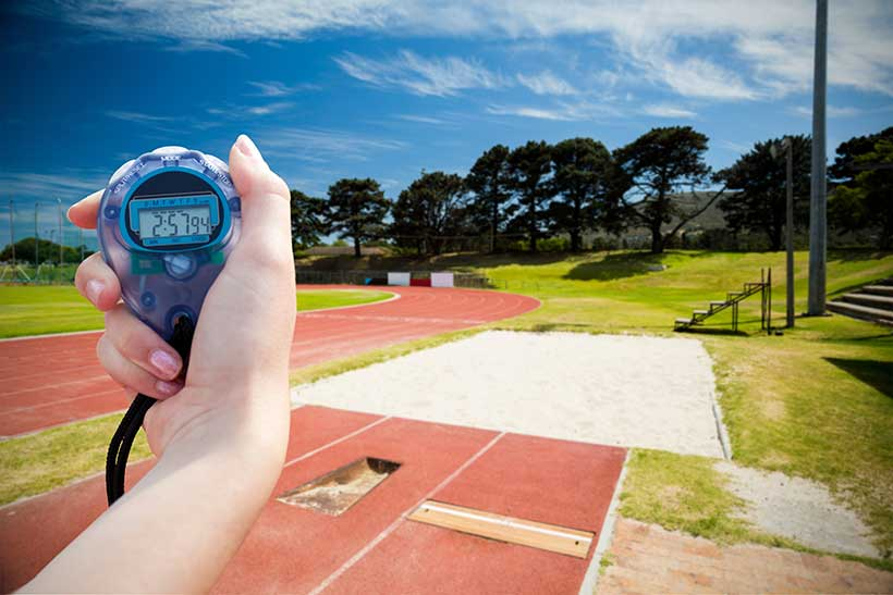 Picture of an athlete with a stopwatch on the athletics track
