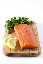 A Salmon Fillet On a Wooden Board Next To Lemon Slices.