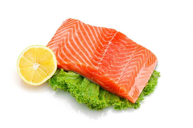 A Large Fillet of Salmon Served Alongside Lettuce and a Lemon Half.
