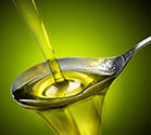 A Picture of Cooking Oil Pouring From a Bottle Onto a Spoon