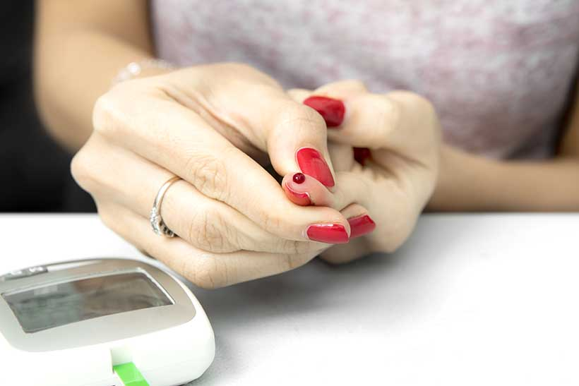Picture of a Lady Next To a Ketone Blood Meter With Blood on Her Finger.