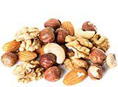 Mixed Nuts on a White Surface Including Almonds and Cashews.