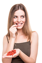 Picture of a Young Woman Eating Goji Berries From Her hand.