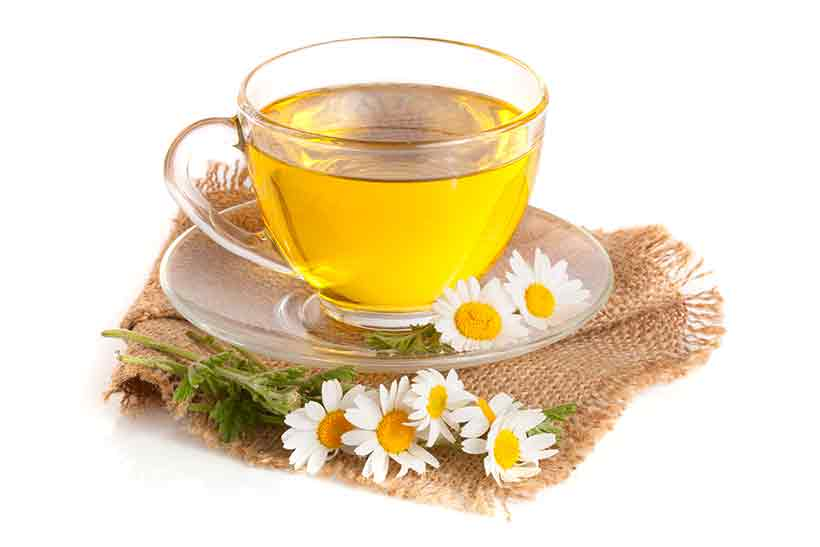 Cup of Chamomile Tea Surrounded by Leaves and Flowers.